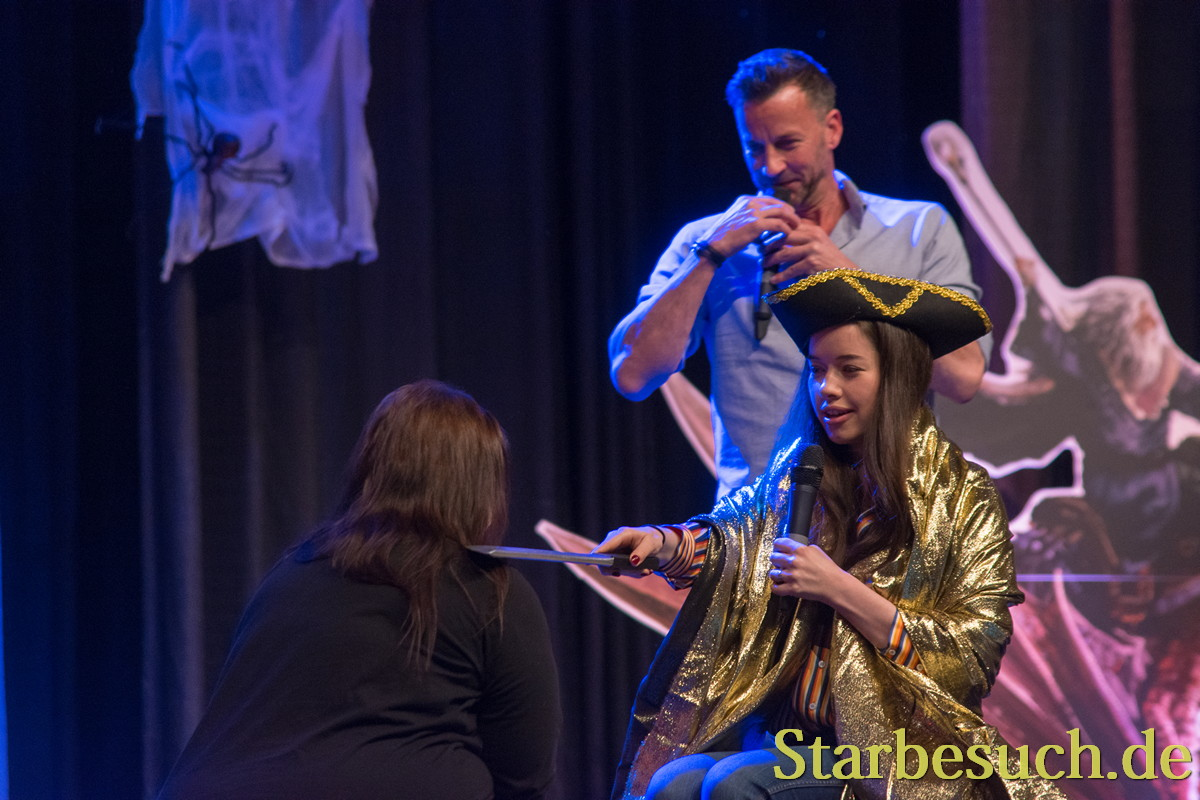 Actors Craig Parker (l), Anna Popplewell (r) knighting a fan at MagicCon 2018