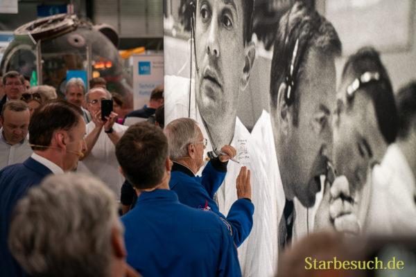 Charlie Duke signiert eine Plakatwand im Technik Museum Speyer